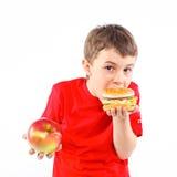 Muchacho que come una hamburguesa. Imagen de archivo libre de regalías