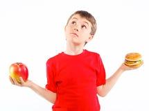 Muchacho que come una hamburguesa. Imágenes de archivo libres de regalías