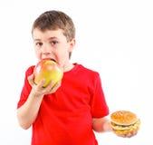 Muchacho que come una hamburguesa. Imagenes de archivo