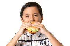 Muchacho que come una hamburguesa Foto de archivo libre de regalías