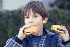 Muchacho que come una hamburguesa Imagen de archivo