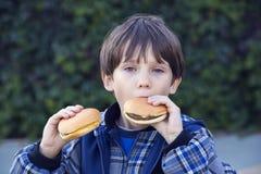 Muchacho que come una hamburguesa Imágenes de archivo libres de regalías