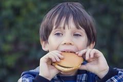 Muchacho que come una hamburguesa Fotos de archivo