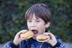 Muchacho que come una hamburguesa Fotografía de archivo libre de regalías