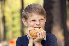 Muchacho que come una hamburguesa Fotos de archivo libres de regalías