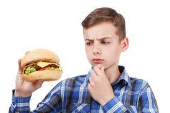 Muchacho que come una hamburguesa Aislado en blanco Fotos de archivo libres de regalías