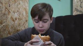 Muchacho que come una hamburguesa en un restaurante El muchacho est? sosteniendo una hamburguesa con carne de vaca almacen de video