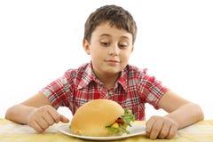 Muchacho que come una hamburguesa grande Fotografía de archivo libre de regalías