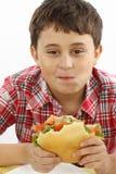 Muchacho que come una hamburguesa grande Foto de archivo