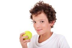 Muchacho que come una manzana verde Foto de archivo