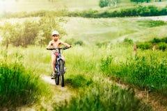 Muchacho que compite con en la bici Imagen de archivo libre de regalías