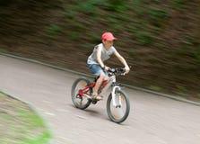 Muchacho que compite con en la bici a través de parque Fotografía de archivo libre de regalías