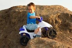 Muchacho que conduce el patio del juguete en terreno Foto de archivo libre de regalías