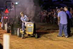 Muchacho que conduce el tractor en la tracción de la competencia Imagenes de archivo