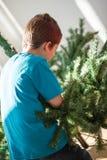 Muchacho que construye un árbol de navidad Imágenes de archivo libres de regalías