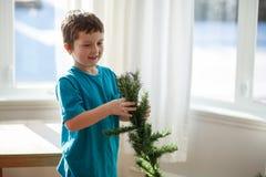 Muchacho que construye un árbol de navidad Foto de archivo