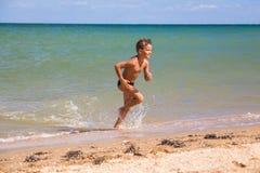 Muchacho que corre del mar en la playa Foto de archivo
