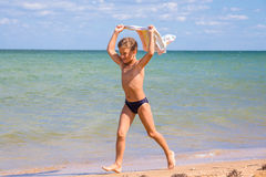 Muchacho que corre en la costa costa con la toalla Fotografía de archivo