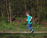 Muchacho que corre a lo largo de la trayectoria de bosque Fotos de archivo libres de regalías