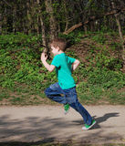 Muchacho que corre a lo largo de la trayectoria de bosque Imagen de archivo