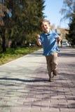 Muchacho que corre a lo largo del camino en parque Foto de archivo libre de regalías