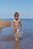 Muchacho que corre a través del agua Fotos de archivo
