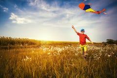 Muchacho que corre a través del campo con la cometa que vuela sobre su cabeza Imagen de archivo libre de regalías