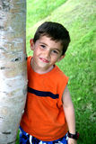 Muchacho que cuelga hacia fuera alrededor de árbol Foto de archivo
