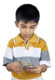 Muchacho que cuenta el dinero con la expresión Imagen de archivo