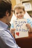Muchacho que da el gráfico del papá. imagenes de archivo