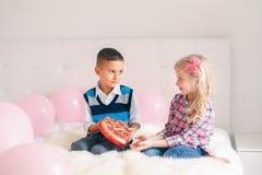 Muchacho que da el presente del regalo del chocolate de la muchacha para celebrar a Valentine Day imagenes de archivo