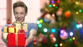 Muchacho que da las cajas de regalo en luces de la Navidad borrosas almacen de video
