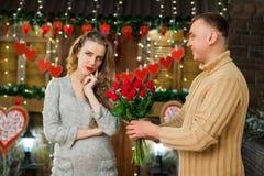 Muchacho que da las flores a su muchacha el día del ` s de la tarjeta del día de San Valentín Fotografía de archivo libre de regalías
