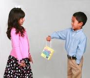Muchacho que da a muchacha un regalo Fotos de archivo