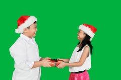 Muchacho que da presentes a su hermana en estudio Imágenes de archivo libres de regalías