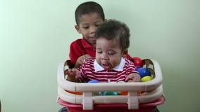 Muchacho que da un abrazo y un beso a su pequeño hermano almacen de video