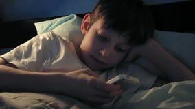Muchacho que descansa en su cama por la tarde y que usa su teléfono elegante almacen de video