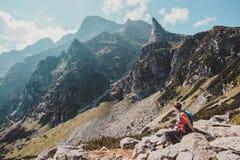 Muchacho que descansa sobre una roca en las montañas Fotografía de archivo libre de regalías