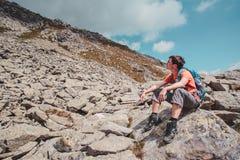 Muchacho que descansa sobre una roca en las montañas Imagen de archivo