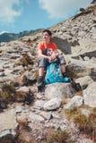 Muchacho que descansa sobre una roca en las montañas Fotos de archivo libres de regalías