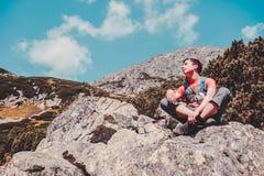 Muchacho que descansa sobre una roca en las montañas Fotografía de archivo