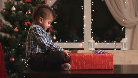 Muchacho que desempaqueta el regalo en la tabla almacen de metraje de vídeo