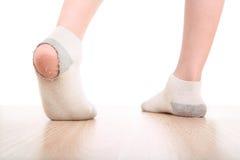 Muchacho que desgasta calcetines sucios con los agujeros en ellos imagen de archivo