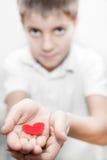 Muchacho que detiene a la tarjeta del día de San Valentín roja del amor del corazón Fotos de archivo libres de regalías