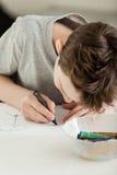 Muchacho que dibuja cuidadosamente con el creyón en el papel Imagen de archivo