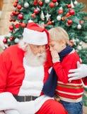 Muchacho que dice deseo en el oído de Papá Noel Imagen de archivo libre de regalías