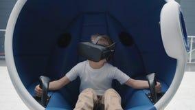 Muchacho que disfruta de la atracci?n de la realidad virtual usando las auriculares de VR en una silla interactiva m?vil almacen de metraje de vídeo
