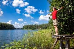Muchacho que disfruta de verano por un lago del bosque Imagenes de archivo