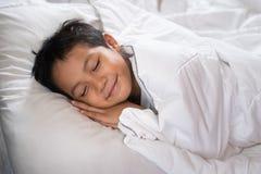 Muchacho que duerme con la cara de la sonrisa en la hoja y la almohada blancas de cama Fotografía de archivo libre de regalías