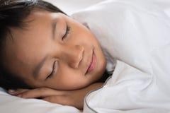 Muchacho que duerme con la cara de la sonrisa en la hoja y la almohada blancas de cama Fotos de archivo libres de regalías